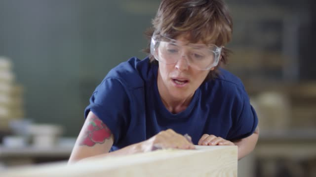 Bидео Female Woodworker Sanding Wood with Sandpaper