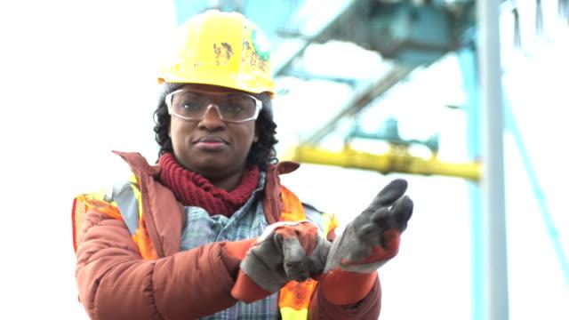 kvinnliga arbetare vid frakt port sätter på arbetshandskar - skyddshandske bildbanksvideor och videomaterial från bakom kulisserna