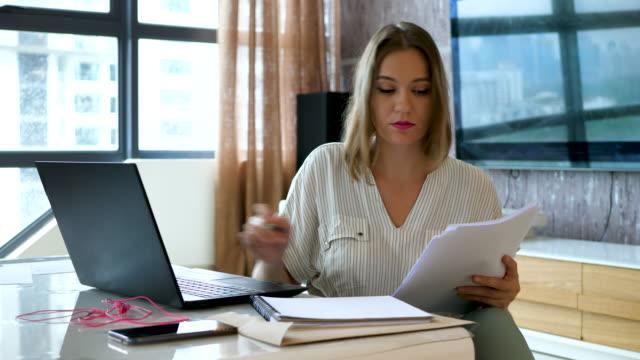 kvinnlig arbetare kontrollerar dokument och indata i bärbar dator - accounting bildbanksvideor och videomaterial från bakom kulisserna