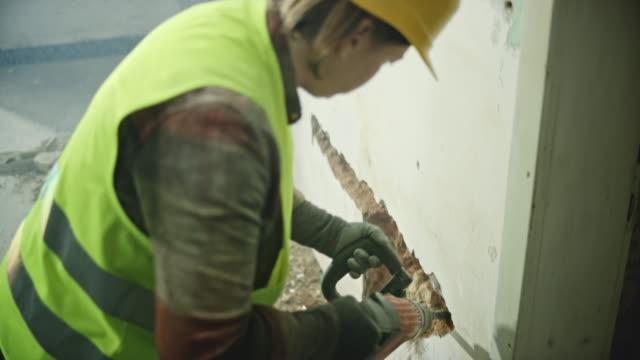 kvinnlig arbetstagare förstör väggen i ett hus med en pneumatisk hammare - construction workwear floor bildbanksvideor och videomaterial från bakom kulisserna