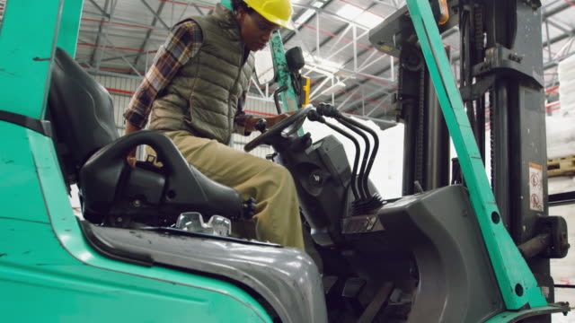 female worker driving forklift in a warehouse - azionare video stock e b–roll