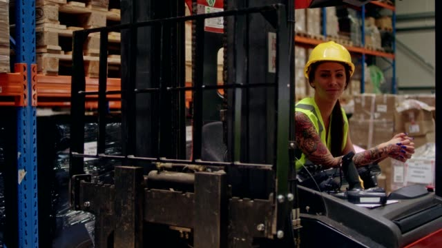 Female worker driving on a forklift. Warehouse video
