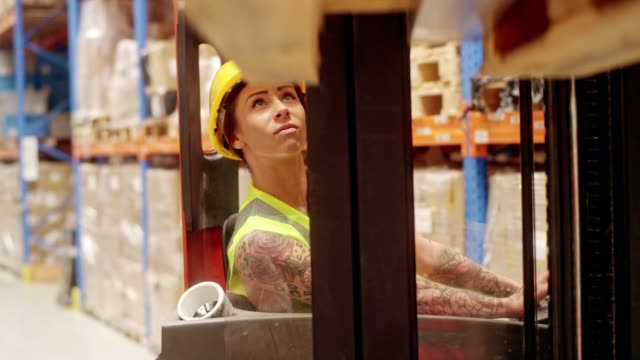 Female worker driving on a forklift. Warehouse Woman in the warehouse driving on a forklift. Picking up cardboard boxes forklift stock videos & royalty-free footage