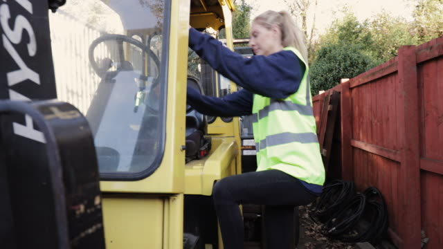 female worker getting into a forklift - apprendista video stock e b–roll