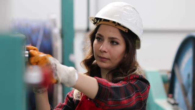 Female worker handling machine in factory Portrait of a serious technician or engineer woman checking pressure device for industry system, opening or closing valve equipment in industrial site factory or utility. authority stock videos & royalty-free footage