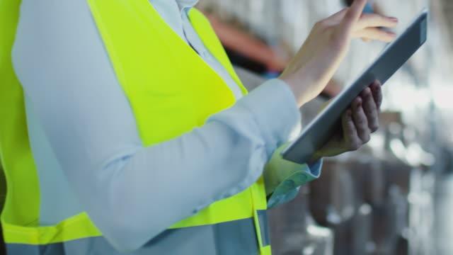 Mujer trabajadora de Logistic Warehouse utiliza Tablet PC - vídeo