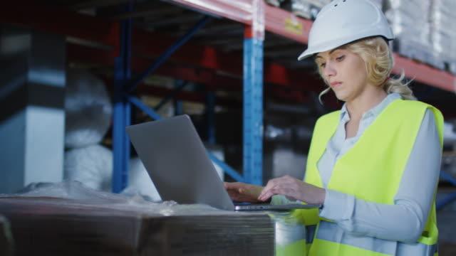 weibliche arbeiter des logistic warehouse arbeiten an laptop wears white hard hat. - kopfbedeckung stock-videos und b-roll-filmmaterial