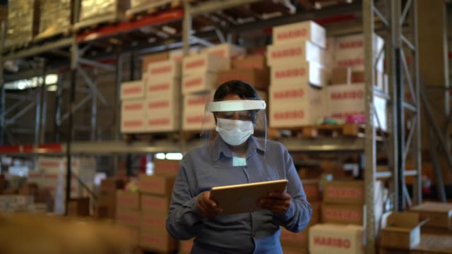 female worker walking and using digital tablet at warehouse - with face mask - prodotti supermercato video stock e b–roll