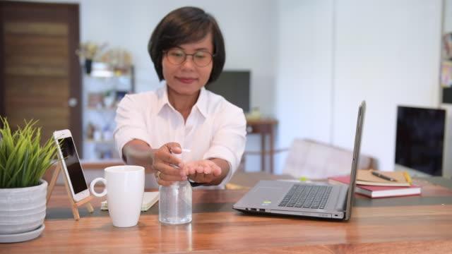 vídeos y material grabado en eventos de stock de trabajadora trabaja en casa aplicando gel antibacteriano desinfectante para prevenir covid 19 - hand sanitizer