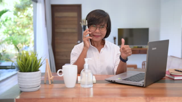 Female worker work from home using laptop and mobile phone applying antibacterial sanitizer gel to prevent Covid 19