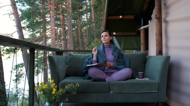 vídeos de stock e filmes b-roll de female writer working on essay while glamping - writing ideas
