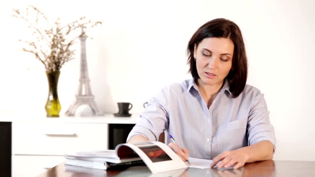 Female writes a letter at the dining room with classic pen-paper method :) video