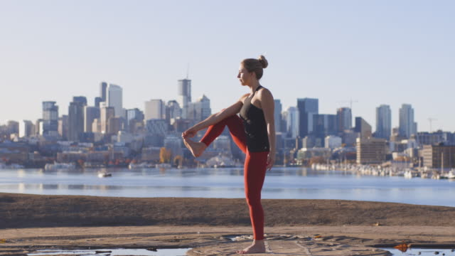 Female Yoga Instructor Doing an Extended Hand to Big Toe Pose Balanced and Relaxed Outdoors in Modern Urban Metropolis