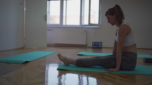 Female yoga instructor leading an online class to her clients during quarantine of coronavirus pandemic