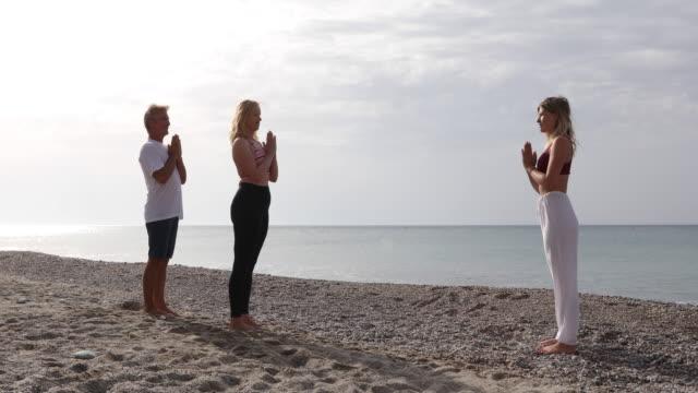 여성 요가 강사가 르 친다 중간 세 커플 요가 이동 - 와이드 샷 스톡 비디오 및 b-롤 화면