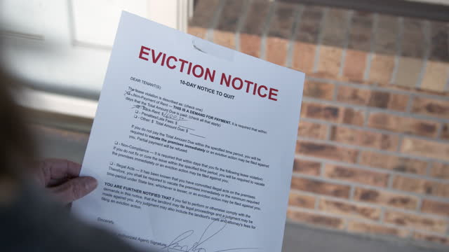 Female's Caucasian Hands Hanging a Paper Eviction Notice on the Front Door of a Rental Home 10-Day Notice to Quit Paper sign foreclosure stock videos & royalty-free footage