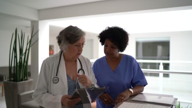 females doctor and nurse talking in hospital secretary and walking - ассистент стоковые видео и кадры b-roll