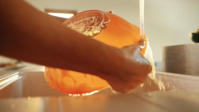vídeos de stock, filmes e b-roll de mãos de fêmeas a tigela laranja sob a filmagem de câmera lenta hd torneira de lavagem - louça