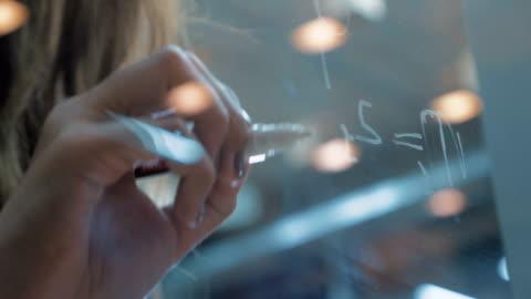 vidéos et rushes de femanine mains écrire sur tableau blanc verre avec le marqueur blanc - en verre