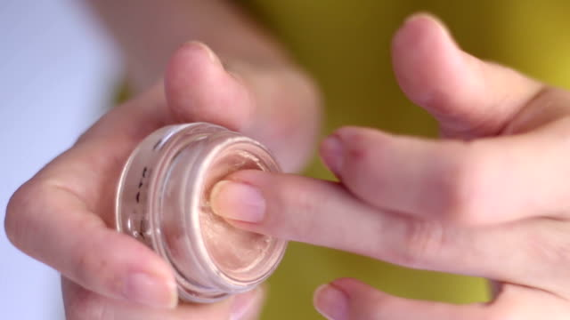 vídeos de stock e filmes b-roll de feminine hand taking cosmetics from jar. close up - brilho labial