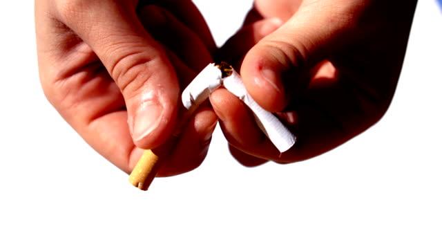 feminina händer skära en cigarett i hälften - släcka bildbanksvideor och videomaterial från bakom kulisserna