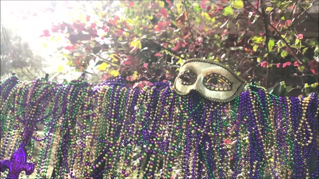 fence covered with carnival beads topped with Mardi Gras Mask