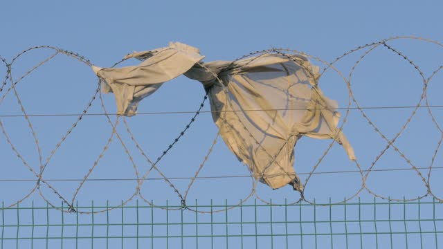 fence prison strict regime. piece of torn clothing fugitive hanging on barbed wire on a windy day. concept illegal immigration refugees