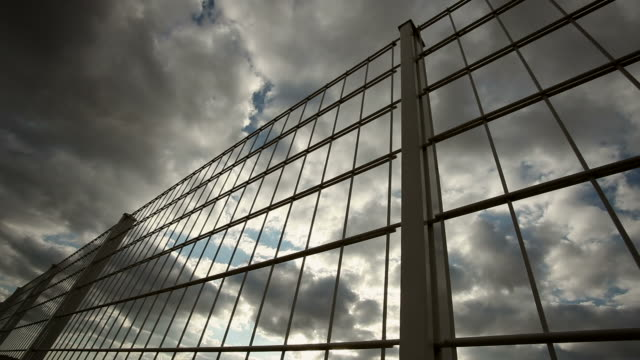 fence with clouds - close up video