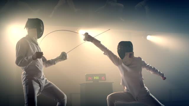 vídeos de stock, filmes e b-roll de esgrimista demonstrando jab, golpe no coração. atletas de esgrima duelam . dois esgrimistas profissionais mostram esgrima magistral em sua luta de folha. filmado na câmera arri alexa em câmera lenta . - campeonato esportivo