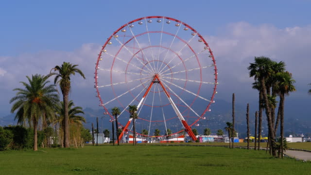 ferris wheel against the blue sky with clouds near the palm trees in the resort town, sunny day - колесо обозрения стоковые видео и кадры b-roll