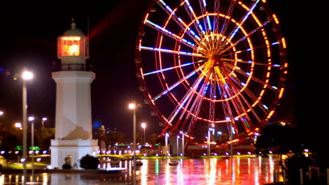 ferris wheel and lighthouse in the miracle park at night on the embankment of batumi - колесо обозрения стоковые видео и кадры b-roll