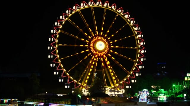 Ferris wheel by night. Blurry, colorful nights from amusement park at night.