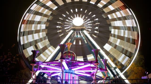 Ferris wheel in amusement Park in festive lights in action. Time lapse