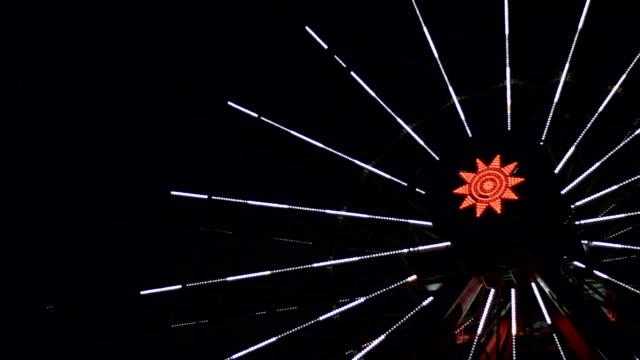 vídeos de stock, filmes e b-roll de roda-gigante no parque de diversões, slow motion vídeo tiro de noite de uma atração de incandescência - áustria