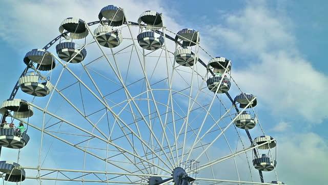 Ferris wheel rotates against the blue sky. People look away