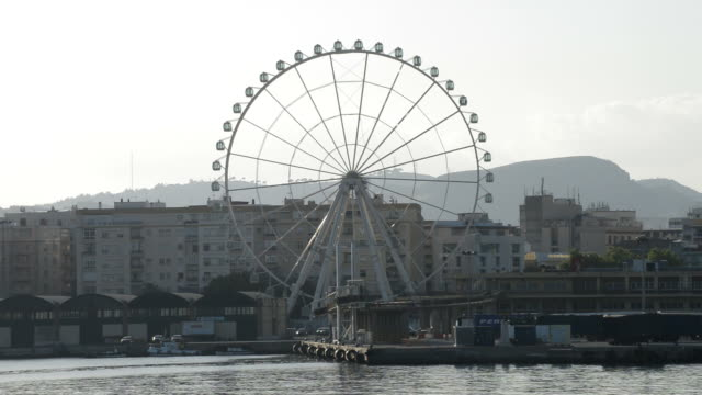 Ferris wheel spinning with buildings of a city at sunset in Malaga, Spain video