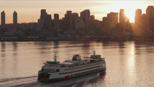 Ferry heading towards Seattle at sunrise. Seattle, Washington circa-2017, Ferry heading towards Seattle at sunrise.  Shot with Cineflex and RED Epic-W Helium. seattle stock videos & royalty-free footage