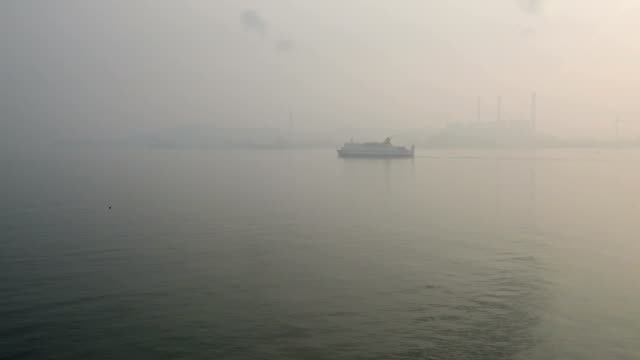ferry moving toward the port of Incheon, Seoul, South Korea on a foggy day with electric power station and Wind turbine power generators silhouettes visible in the mist. video