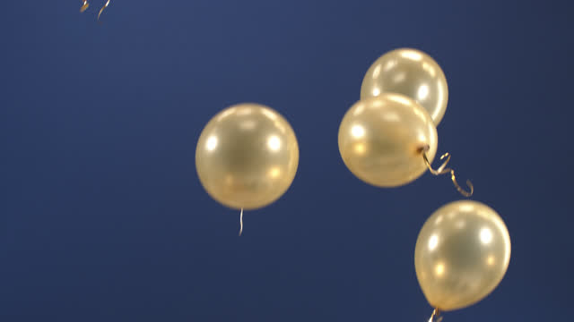 Festive decoration - balloons - fly up in the video as a surprise for the holidays: Valentine's Day, Birthday, Christmas, a gala event or New Year on a blue background. video