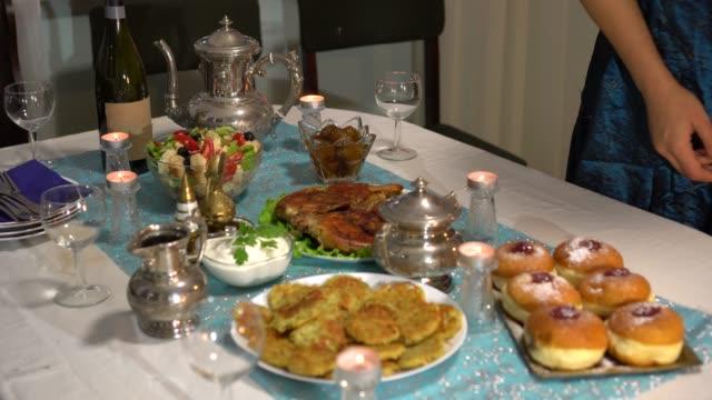 vídeos y material grabado en eventos de stock de cena familiar festiva. comida tradicional de hanukkah. en la mesa hay una comida frita simbólica kosher kosher. latkes, rosquillas rellenas de gelatina, productos lácteos, ensalada con queso, gelt de chocolate hanukkah - hanukkah