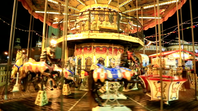 festive merry-go-round whirling and sparkling lights near at red square - luna park video stock e b–roll
