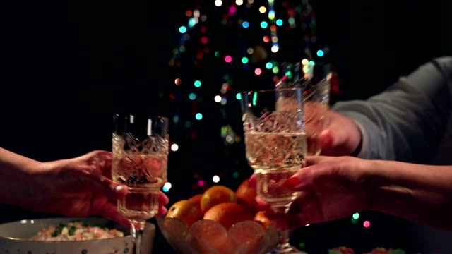 vídeos de stock e filmes b-roll de festive new year's feast guests raise their glasses and drink champagne - enjoying wealthy life