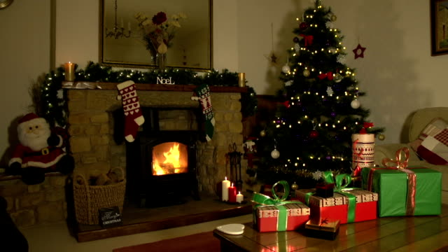 stockvideo's en b-roll-footage met festive room at christmas with presents, tree and fireplace - fireplace