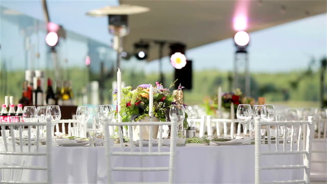 Festive table elegantly served in a luxurious outdoor terrace restaurant. Wedding table setting with glasses candles and flowers video