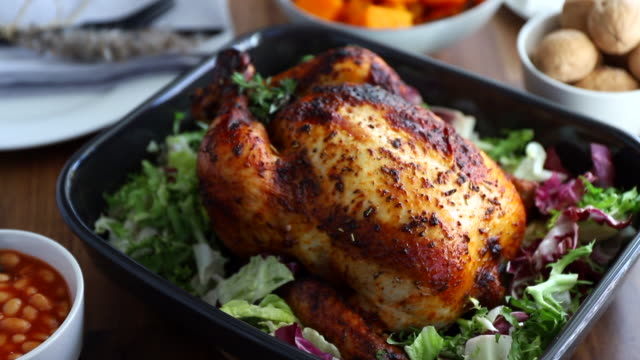 festive table with whole roasted chicken, pumpkin and mushrooms. thanksgiving or celebration dinner concept - pranzo di natale video stock e b–roll