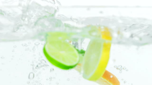 A few lemon, lime and ornage pieces fall into the water