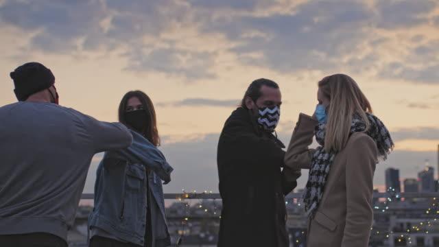 stockvideo's en b-roll-footage met vrienden ontmoeten elkaar tijdens pandemieën van coronavirus. elleboogstoten. zonsondergang op het dak - bord bericht