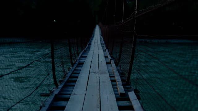 A fictional character walks along a swinging suspension bridge.