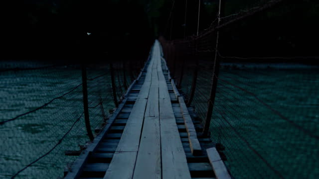 A fictional character walks along a swinging suspension bridge. A fictional character is walking along a swinging suspension bridge that hangs over the river. suspension bridge stock videos & royalty-free footage