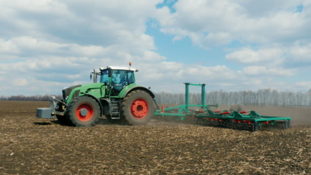 Field work in early spring. On a sunny day, the tract pulls the harrow. Tracking 3 axis stabilized video video